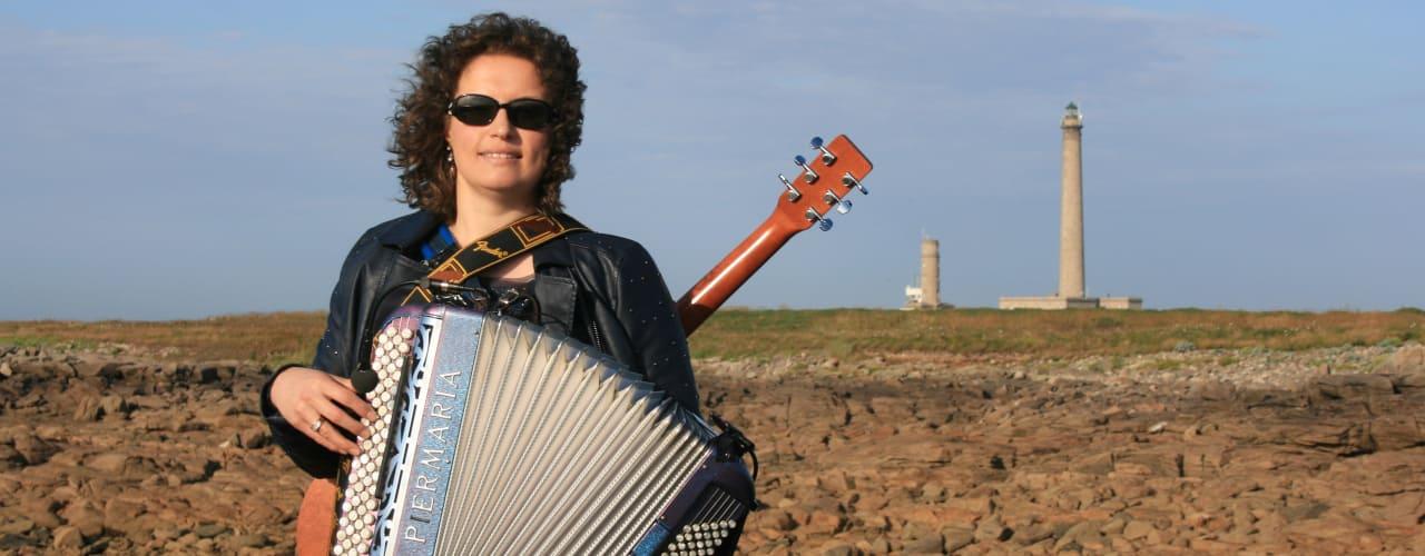 Gwenn avec son accordéon et sa guitare devant le phare de Gatteville